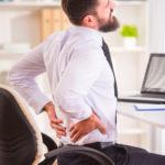 Mann hat Rückenschmerzen wegen falschem Bürostuhl